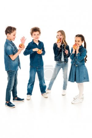 Photo for Full length view of children in denim clothes eating apples on white - Royalty Free Image