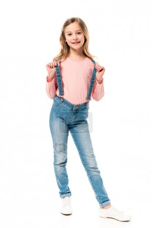 full length view of kid in jeans looking at camera with smile isolated on white
