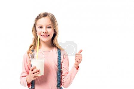 Lächelndes Kind hält Milchshake in der Hand und zeigt den Daumen vereinzelt auf weiß