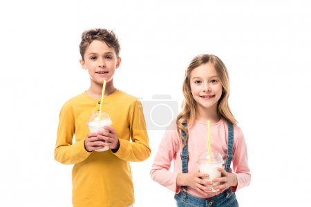 Foto de Two smiling kids holding milkshakes isolated on white - Imagen libre de derechos