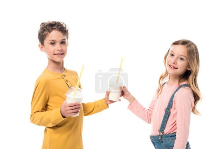 Photo for Two smiling kids holding milkshakes isolated on white - Royalty Free Image
