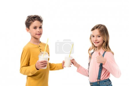 Foto de Two kids holding milkshakes and showing thumb up isolated on white - Imagen libre de derechos