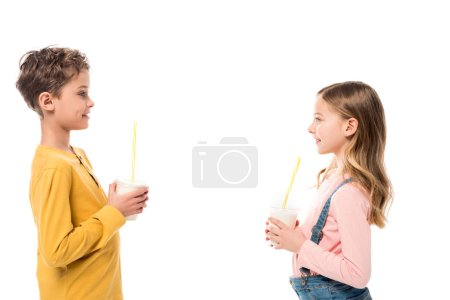 Photo for Side view of two kids holding milkshakes and looking at each other isolated on white - Royalty Free Image