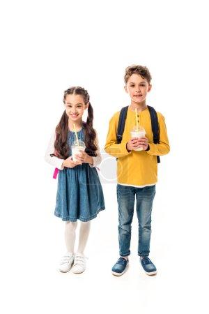 Photo pour Vue pleine longueur de deux gosses retenant des milkshakes isolés sur le blanc - image libre de droit