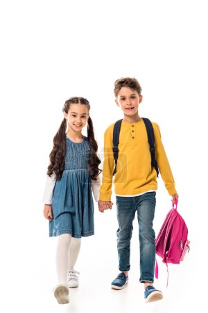 Foto de Full length view of schoolchildren with backpacks holding hands isolated on white - Imagen libre de derechos