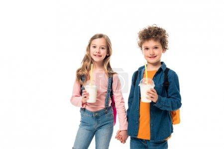Photo pour Écoliers avec sacs à dos et milkshakes tenant les mains isolées sur blanc - image libre de droit