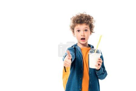 Photo for Shocked schoolkid holding milkshake and showing thumb up isolated on white - Royalty Free Image