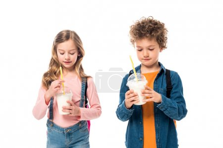 Photo for Two schoolkids with backpacks holding milkshakes isolated on white - Royalty Free Image