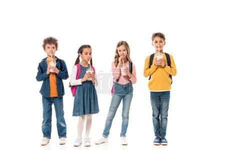 Foto de Vista a lo largo de los escolares que beben batidos aislados en blanco - Imagen libre de derechos