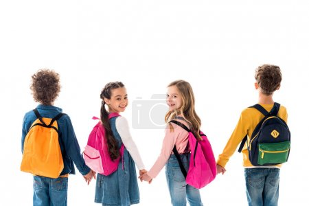 Foto de Schoolchildren with backpacks holding hands and looking back isolated on white - Imagen libre de derechos