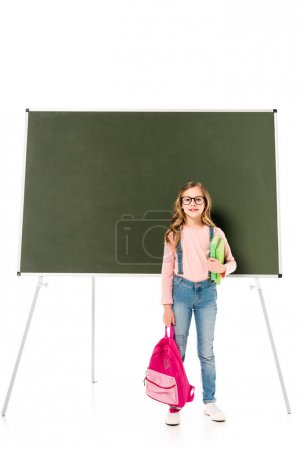 Photo for Full length view of schoolgirl in glasses holding backpack and books near blackboard isolated on white - Royalty Free Image