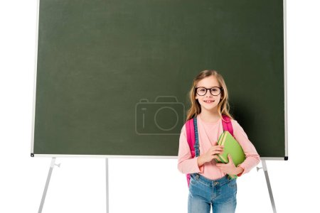 Photo for Front view of schoolgirl with backpack and books standing near blackboard isolated on white - Royalty Free Image