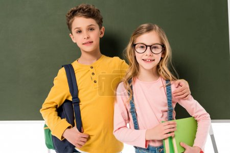 Photo for Two schoolchildren with backpacks and books standing near blackboard isolated on white - Royalty Free Image