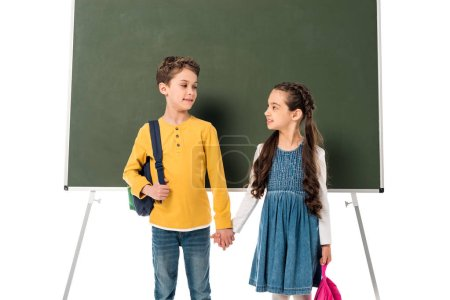 Foto de Two schoolchildren with backpacks holding hands near blackboard isolated on white - Imagen libre de derechos