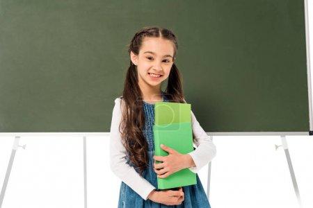 Photo for Smiling schoolgirl holding books near blackboard isolated on white - Royalty Free Image