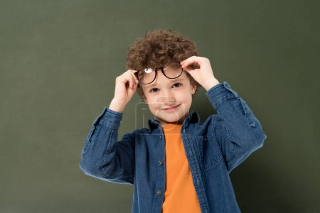 Photo for Smiling curly kid with glasses looking at camera isolated on green - Royalty Free Image