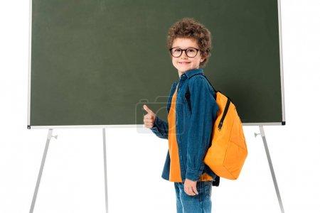 Foto de Sonriente colegial en gafas de pie cerca de la pizarra y mostrando el pulgar hacia arriba aislado en blanco - Imagen libre de derechos