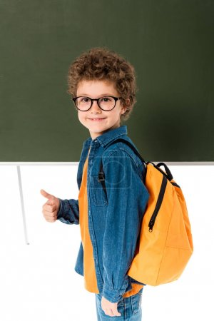 Photo for High angle view of smiling schoolboy in glasses standing near blackboard and showing thumb up isolated on white - Royalty Free Image