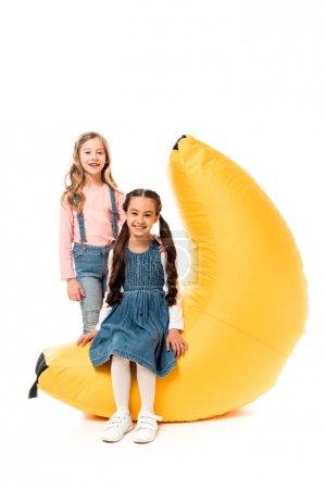 Foto de Two smiling kids with bean bag chair on white - Imagen libre de derechos