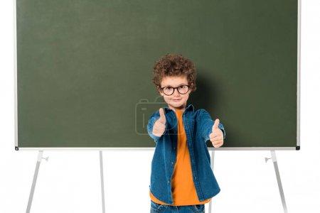 Photo pour Écolier de sourire dans des glaces restant près du tableau noir et affichant des pouces vers le haut d'isolement sur le blanc - image libre de droit