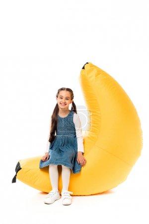 Foto de Kid in casual clothes sitting on bean bag chair on white - Imagen libre de derechos