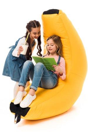 Foto de Two smiling kids with bean bag chair reading book on white - Imagen libre de derechos