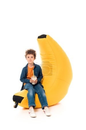 Foto de Kid in casual clothes sitting on bean bag chair and holding milkshake on white - Imagen libre de derechos