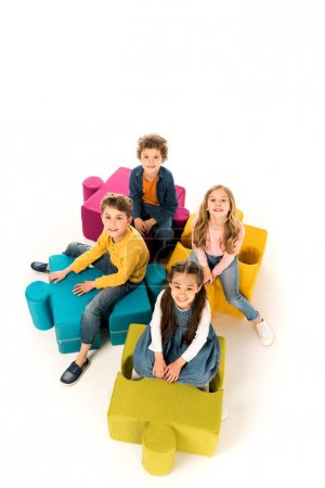 Photo for Overhead view of kids sitting on jigsaw puzzles on white - Royalty Free Image
