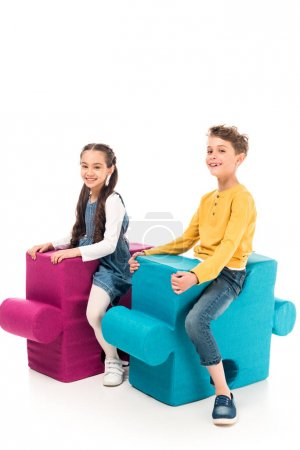 Photo for Smiling kids sitting on big jigsaw puzzles isolated on white - Royalty Free Image