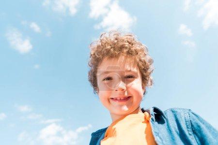 Photo pour Vue à angle bas de l'enfant bouclé souriant sous le ciel bleu - image libre de droit
