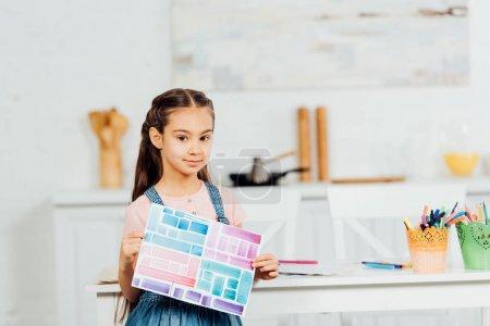 Photo pour Le papier mignon de fixation d'enfant avec des rayures colorées tout en restant près de la table à la maison - image libre de droit