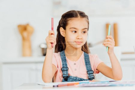 Photo for Cute kid choosing between turquoise and red felt pens at home - Royalty Free Image