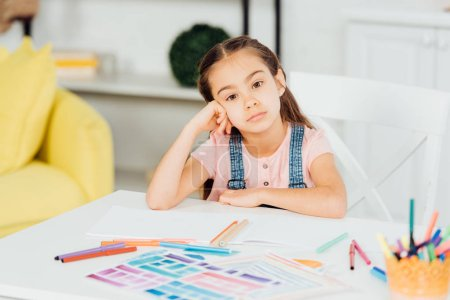 Photo for Selective focus of upset kid looking at camera near papers with drawing - Royalty Free Image
