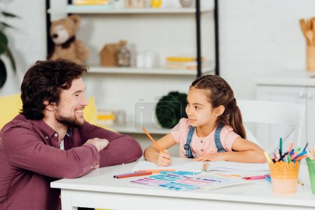Photo for Happy father and cheerful and cute daughter looking at each other at home - Royalty Free Image