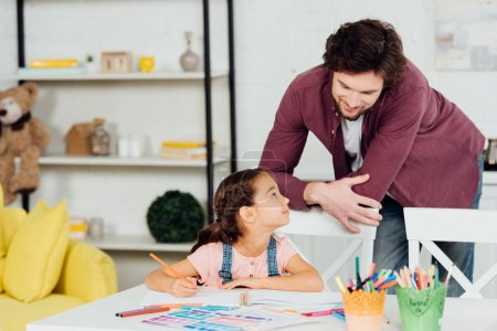 Photo for Handsome father standing near cute daughter holding color pencil at home - Royalty Free Image