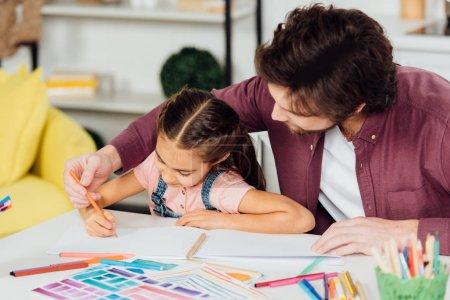 Photo pour Père barbu aidant le dessin mignon de fille sur le papier - image libre de droit