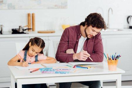 Photo pour Beau père et mignon descendant dessinant sur des papiers à la maison - image libre de droit