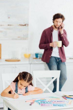 Photo pour Foyer sélectif du dessin mignon d'enfant sur le papier près du père parlant sur le smartphone et retenant la tasse - image libre de droit