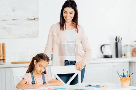Photo for Attractive mother looking at cute daughter drawing at home - Royalty Free Image