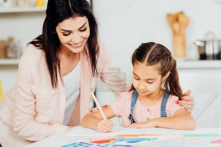 Photo for Happy mother looking at cute daughter drawing on paper at home - Royalty Free Image