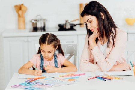 Photo pour Femme heureux regardant le dessin de descendant sur le papier à la maison - image libre de droit