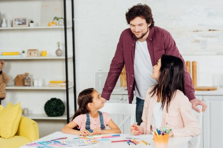 Photo for Cheerful man looking at brunette wife and daughter at home - Royalty Free Image