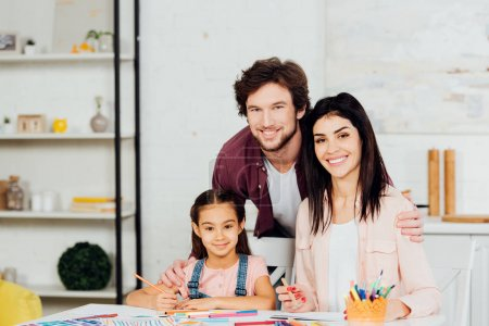 Photo for Happy man and woman smiling with cute daughter and looking at camera - Royalty Free Image