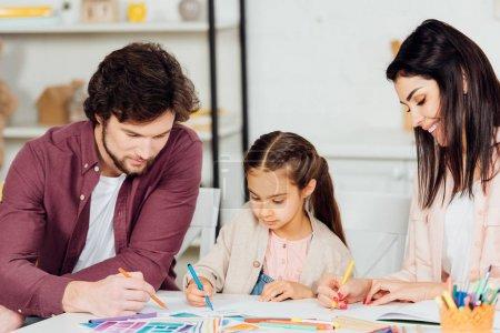 Photo pour Mère heureuse dessinant près de la fille et du mari mignons à la maison - image libre de droit