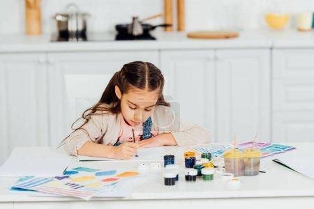 Photo pour Peinture concentrée et mignonne d'enfant sur le papier à la maison - image libre de droit