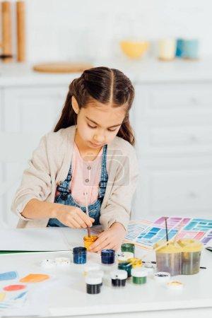 Photo pour Enfant mignon regardant la peinture jaune tout en retenant le pinceau à la maison - image libre de droit