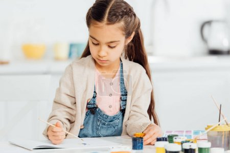 Photo for Focused kid drawing with paintbrush on paper at home - Royalty Free Image