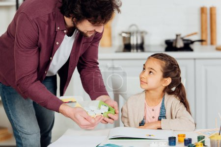 Photo for Happy father holding box with gouache jars near cute daughter - Royalty Free Image