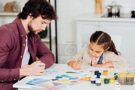 Photo pour Beau père et dessin mignon de descendant avec des pinceaux à la maison - image libre de droit