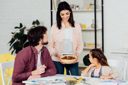 Photo for Cheerful mother holding bowl with cookies near husband and daughter - Royalty Free Image